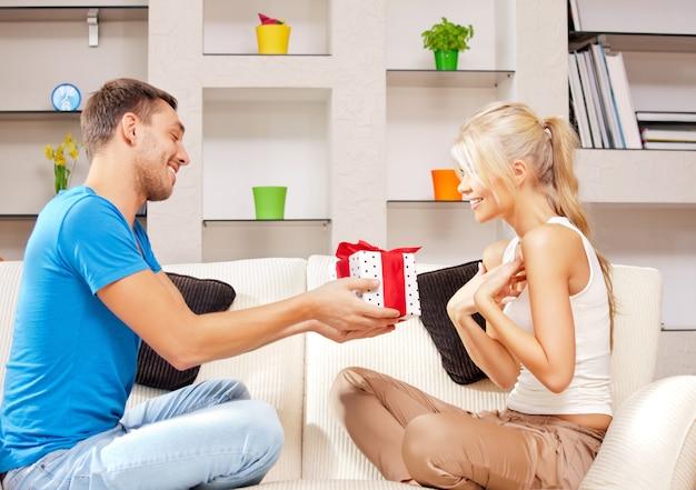 Helles bild eines glücklichen romantischen paares mit geschenk (fokus auf frau)