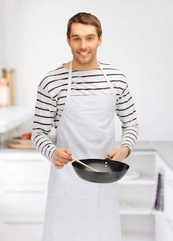 Helles bild eines gutaussehenden mannes mit pfanne in der küche