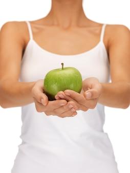 Helles bild von weiblichen händen mit grünem apfel