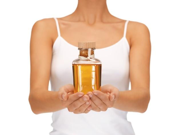 Helles bild von weiblichen händen mit ölflasche