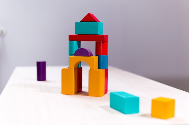 Helles buntes holzklotzspielzeug. ziegelkinder bauen turm, schloss, haus.