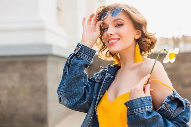 Helles buntes porträt der schönen jungen frau, die in der fröhlichen stimmung mit einem glücklichen lächeln schaut und stilvolle hipster-sonnenbrille, frühlingssommer-modetrend, jeansjacke, gelbes oberteil trägt