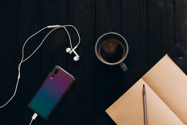 Helles buntes smartphone auf einem schwarzen holztisch. morgen tasse kaffee.