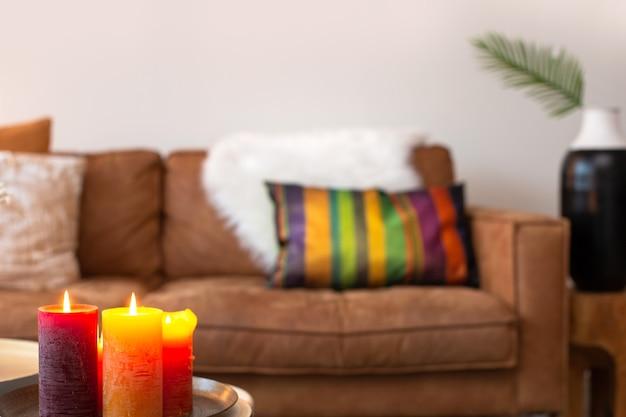 Helles, farbenfrohes wohnzimmer mit sofa im hintergrund mit brennenden kerzen