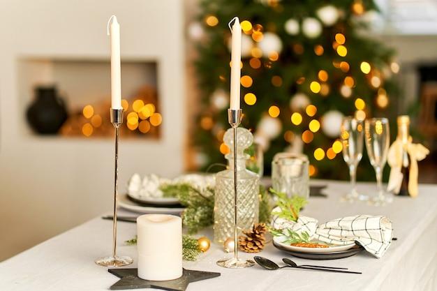 Helles festliches weihnachtsinterieur, gedeckter tisch für ein festliches abendessen.
