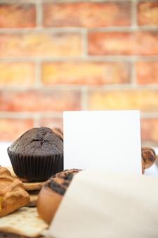 Helles gebäckfotomodell mit weißer leerer listenvorlage und muffin im stadtcafé