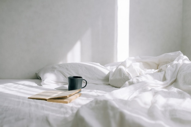 Helles gemütliches schlafzimmer, kaffee- oder teetasse und ein offenes buch auf dem bett.