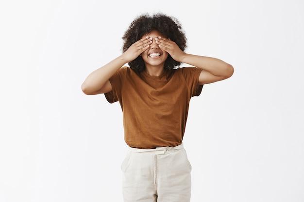 Helles glückliches und junges attraktives afroamerikanisches kurzes mädchen mit afro-frisur, die augen mit handflächen bedeckt und sorglos lächelt, als ob sie verstecken spielen und in spielerischer stimmung suchen
