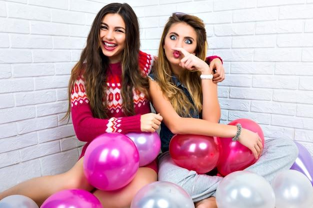 Helles innenporträt von zwei lustigen wettefreunden schwester-hipster-frauen, die verrückt werden, partyzeit, rosa ballon, umarmungen und spaß haben, schwestern, verwandte, feiertage.