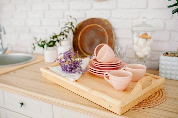 Helles interieur der holzküche. schöne innenausstattung der küche. hellrosa geschirr teller tassen