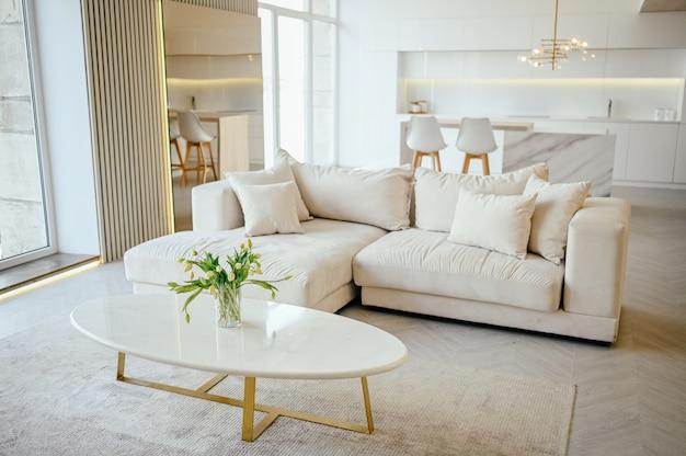 Helles klassisches, modernes luxus-esszimmer und küche im skandinavischen stil mit details aus holz, weiß und marmor, neuen stilvollen möbeln, gemütlicher sofa-couch und minimalistischem nordischem innendesign.