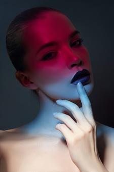 Helles kontrastierendes schönheitsmake-upporträt einer frau in den blauen und roten schattentönen. perfektes make-up für haut und gesicht, dunkler lippenstift auf prallen lippen