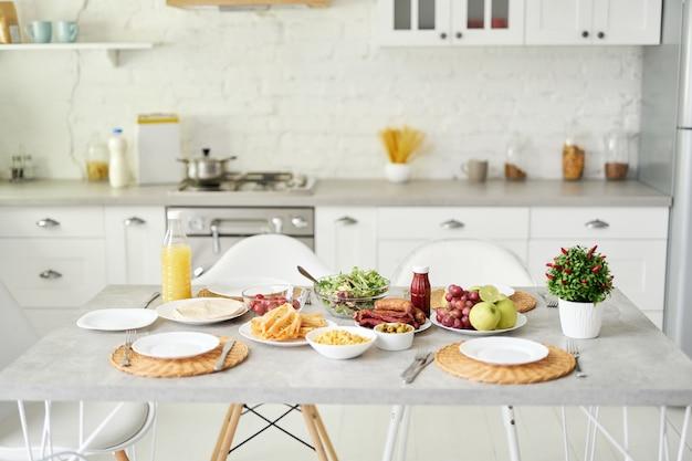 Helles küchenfrühstück im lateinischen stil auf dem tisch modernes helles weißes kücheninterieur mit holz