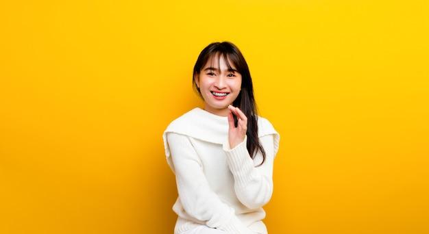 Helles lächeln porträt einer schönen asiatischen geschäftsfrau, die getrennt steht und lächelt. auf gelbem grund