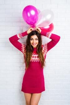 Helles lustiges lebensstilbild zur hübschen jungen frau im lässigen trendigen pullover, der spaß hat und partyballons hält.