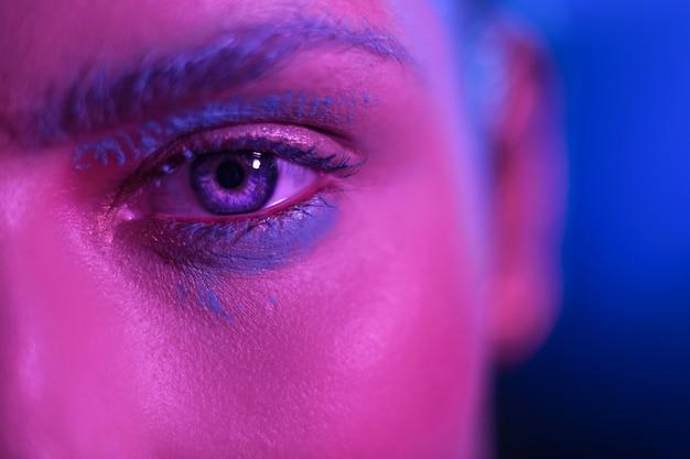 Helles make-up stilvolles mädchenmodell mit blauen augen auf einem blauen hintergrund.