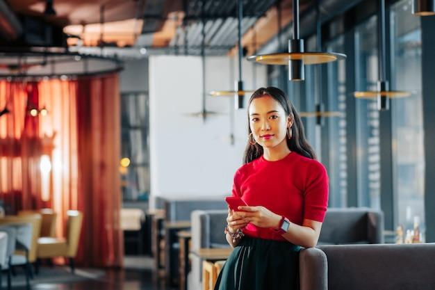Helles modernes restaurant schlanke, dunkelhaarige, stilvolle frau, die in einem hellen, modernen restaurant steht?