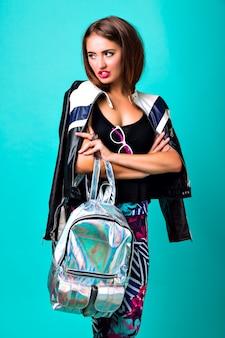 Helles neonmodeporträt der frechen trendigen frau, lederjacke, rucksack, junges modell
