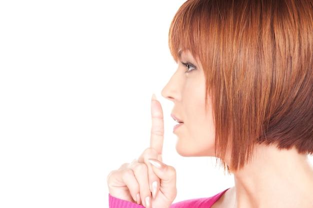Helles porträt der geschäftsfrau mit dem finger auf den lippen