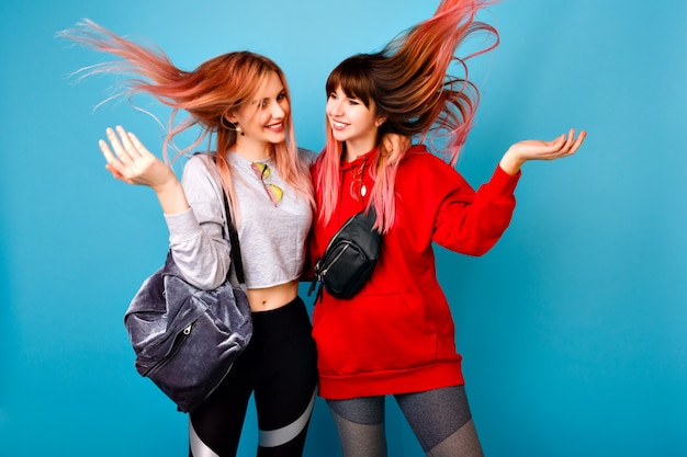 Helles porträt von zwei glücklichen frau, die lächelt und spaß hat, ihre haare hochwirft, sportliche fitnesskleidung und taschen trägt.