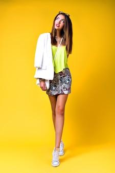 Helles positives modeporträt der hübschen jungen frau, des stilvollen trendigen neon-outfits, der schlauen lässigen, niedlichen emotionen, des farbpop