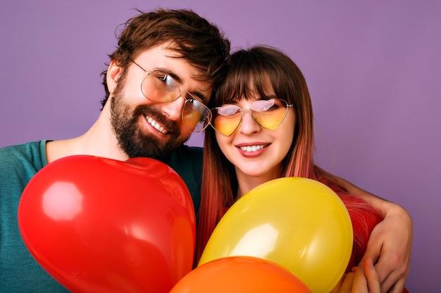 Helles positives porträt des glücklichen hübschen paares, das lächelt, friedensgeste zeigt und partyballons, familienbeziehung, violette wand hält