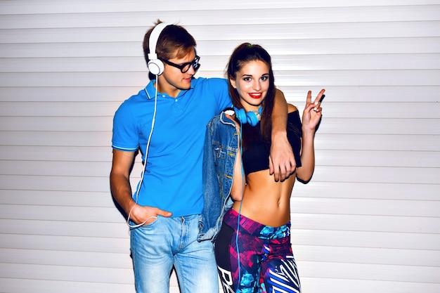 Helles positives porträt des hübschen sexy hipster-paares, das zusammen verrückt wird, helle kleidung und accessoires, positive spielerische gefühle, freude, party. sportlicher urbaner streetstyle-look