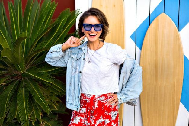 Helles positives porträt des sommerfrühlings der glücklichen lächelnden brünetten frau, die trendiges weibliches hipster-outfit trägt, das lächelt und spaß hat und vor surfbrettern und palmen posiert.
