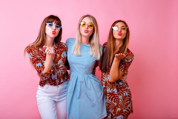 Helles positives porträt von drei glücklichen hipster-frauen, die spaß haben und luftküsse, farblich passende sommerkleidung und bunte sonnenbrille senden,