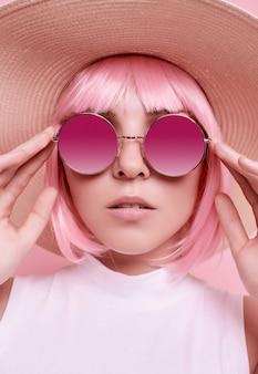 Helles sommerporträt eines positiven, wunderschönen mädchens mit rosa haaren, sonnenbrille und geflochtenem hut auf buntem studio
