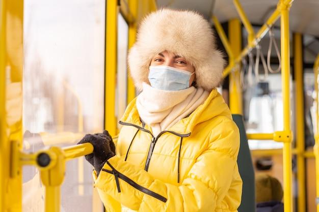 Helles sonniges porträt einer jungen frau in der warmen kleidung in einem stadtbus an einem wintertag