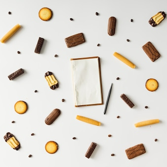 Helles süßes snackmuster mit vintage-notizbuch. flach liegen.