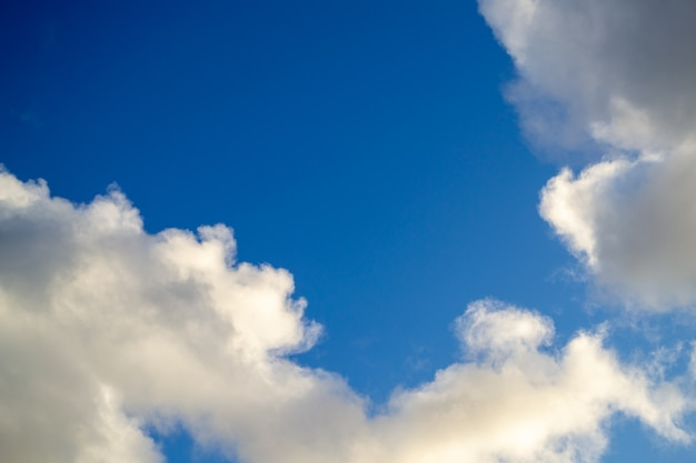 Helles weiß mit grauen wolken auf blauem himmel.