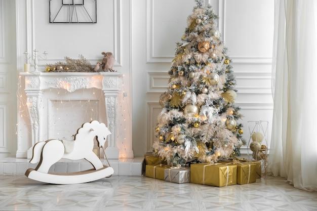 Helles zimmer mit weihnachtlichem interieur, hellem dekor mit künstlichem kamin und schaukelpferdestuhl