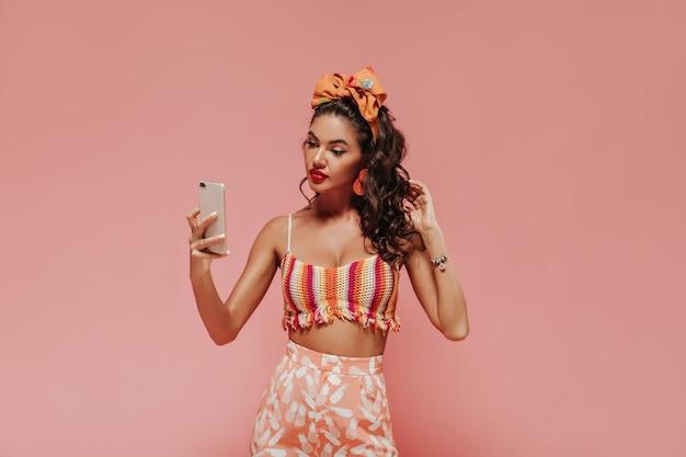 Hellgebräunte frau mit orangefarbenem bandana und stilvollen ohrringen in gestreiftem oberteil und bedruckter rosa hose macht selfie an isolierter wand