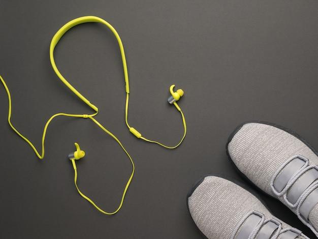 Hellgelbe kabelgebundene kopfhörer und graue turnschuhe auf grauem hintergrund. sportlicher lebensstil. farben 2021.