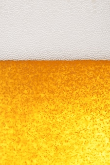 Hellgelber bierhintergrund mit schaum und blasen