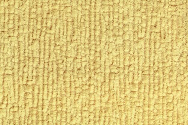 Hellgelber flauschiger hintergrund aus weichem, flauschigem stoff. beschaffenheit der textilnahaufnahme.