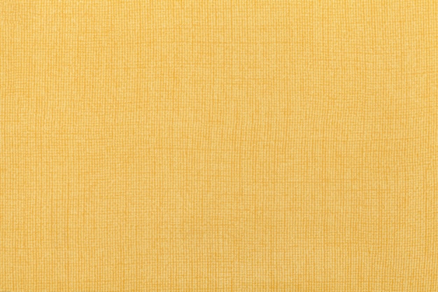 Hellgelber ockerfarbener hintergrund aus einem textilmaterial. stoff mit natürlicher textur. hintergrund.