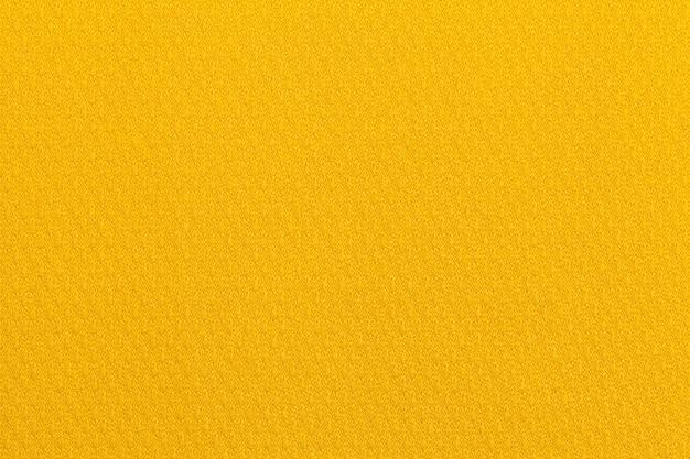 Hellgelber ockerfarbener hintergrund aus einem textilmaterial.