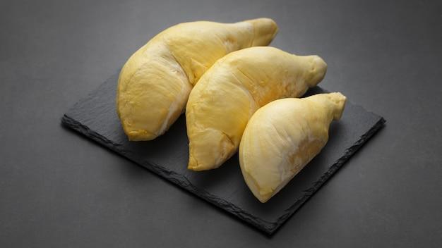 Hellgelbes durian-monatsfleisch auf schiefer und dunklem texturhintergrund, könig der früchte