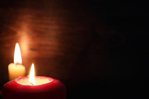 Hellgelbes licht einer brennenden kerzenflamme im dunkeln