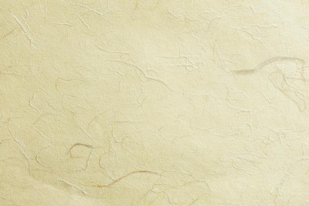 Hellgoldener strukturierter hintergrund aus pergament