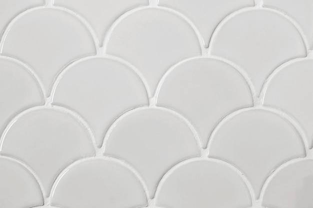 Hellgraue keramikfliesen in form von schuppen. mosaikfliesen an der wand