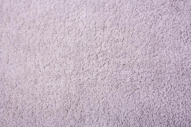 Hellgraue textur der haarigen badematte. sicht von oben