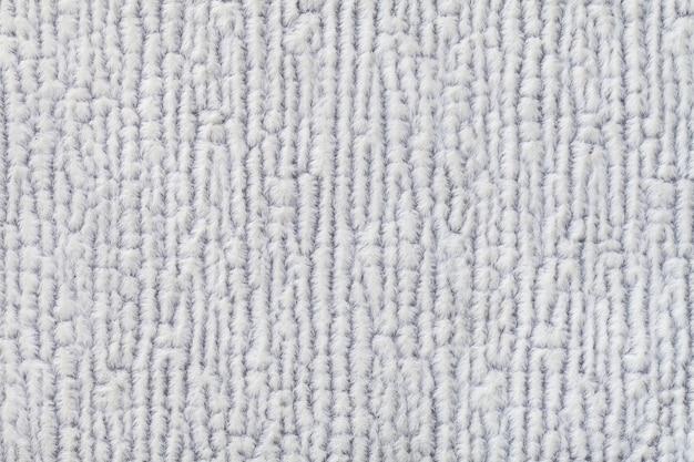 Hellgrauer flaumiger hintergrund der weichen, flaumigen stoffbeschaffenheit der textilnahaufnahme