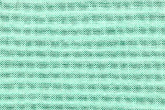 Hellgrüner hintergrund aus einem textilmaterial mit flechtmuster,
