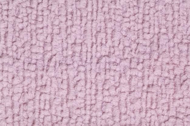 Hellpurpurner flauschiger hintergrund aus weichem, flauschigem stoff. beschaffenheit der textilnahaufnahme.