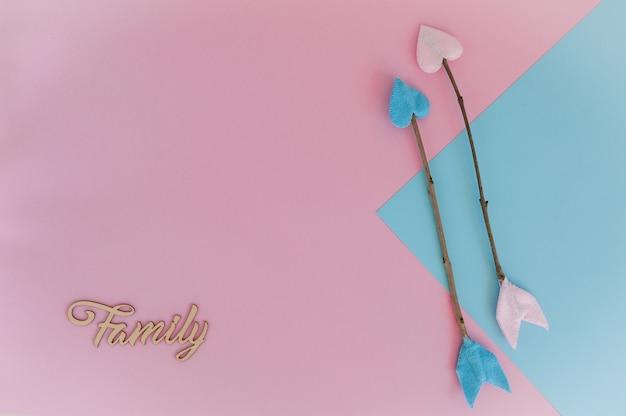 Hellrosa blauer hintergrund mit zweigpfeilen und hölzerner buchstaben familie