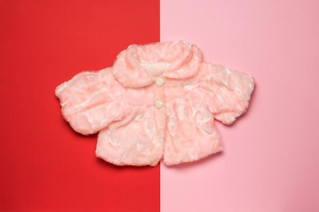 Hellrosa damenpelzcape auf rosa und rotem grund. flach liegen.